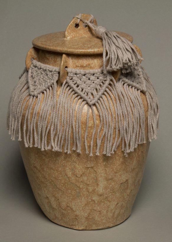 Urna na prochy w kolorze beżowym, ozdobiona makramą.
