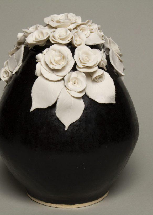 Urna na prochy w kolorze czarnym ozdobiona bukietem róż z porcelany