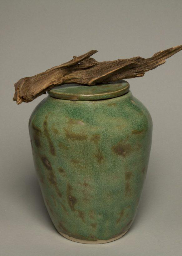 Urna na prochy w kolorze wodnej zieleni z kawałkiem korzenia na pokrywce.